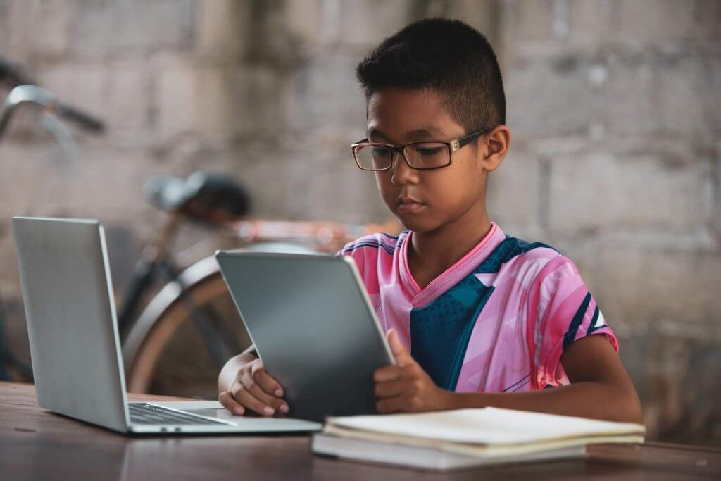Indian boy taking online school classes using tablet and laptop